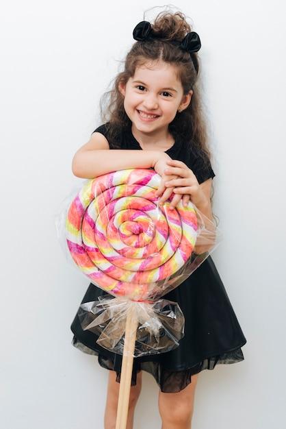 Śliczna mała dziewczynka z gigantycznym lizakiem Darmowe Zdjęcia