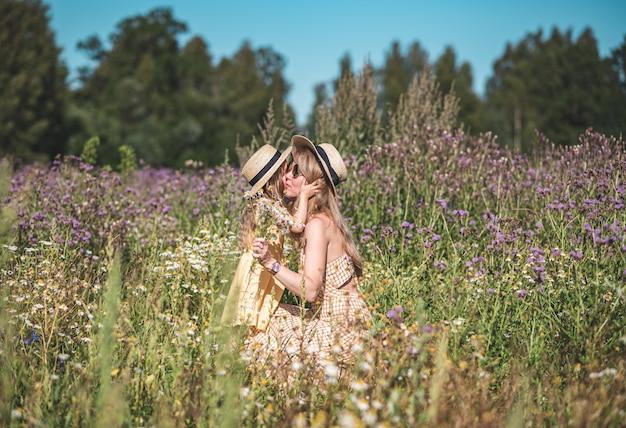 Śliczna Mała Dziewczynka Z Jej Matką Chodzi W Kwiatu Polu Premium Zdjęcia