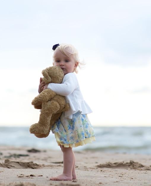Śliczna Mała Dziewczynka Z Misiem Na Plaży Premium Zdjęcia