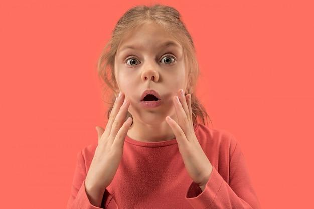 Śliczna Mała Zaskoczona Dziewczyna W Koralowej Sukience Z Długimi Włosami, Uśmiechając Się Darmowe Zdjęcia