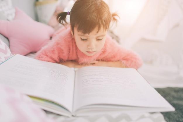 Śliczna Małe Dziecko Dziewczyna Czyta Książkę W Domu. śmieszne Piękne Dziecko Zabawy W Pokoju Dziecięcym. Premium Zdjęcia