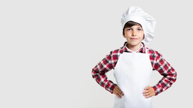 Śliczna młoda chłopiec pozuje jako szef kuchni Darmowe Zdjęcia