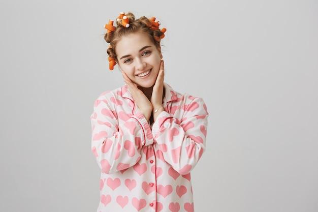 Śliczna Młoda Dziewczyna Dotyka Czystej Skóry, Ubrana W Piżamę I Lokówki Darmowe Zdjęcia