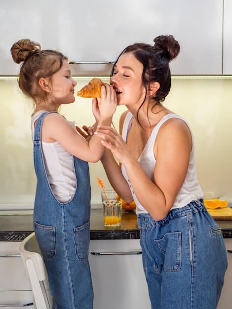 Śliczna Młoda Dziewczyna Dzieli Croissant Z Matką Darmowe Zdjęcia