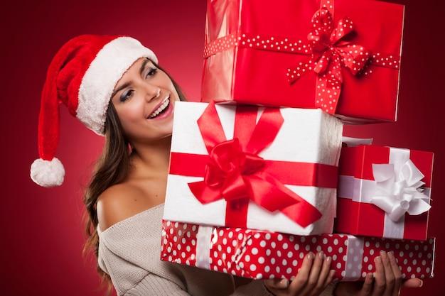 Śliczna Młoda Kobieta Ubrana W Santa Hat Trzyma Prezenty świąteczne Darmowe Zdjęcia