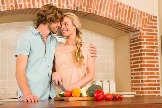 Śliczna para pokrajać warzywa w kuchni Premium Zdjęcia