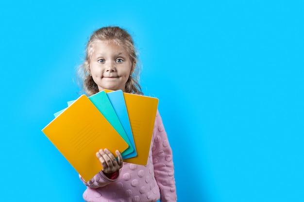 Śliczna rozochocona dziewczyna z wgłębieniami na jej policzkach i kędzierzawym włosy trzyma kolorowych szkolnych notatniki na błękicie Premium Zdjęcia