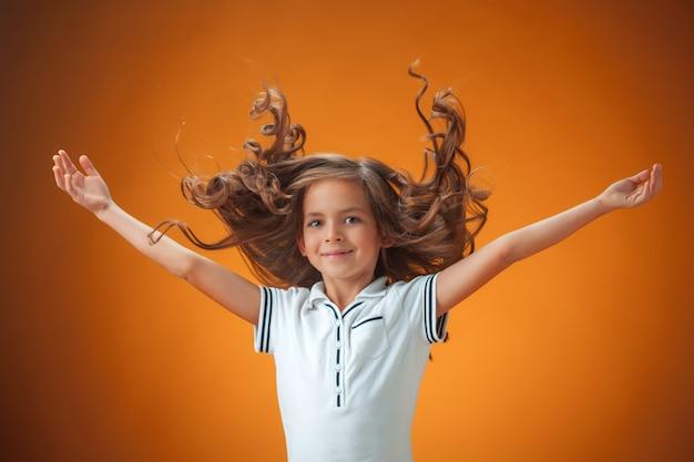 Śliczna Rozochocona Mała Dziewczynka Na Pomarańczowym Tle Darmowe Zdjęcia