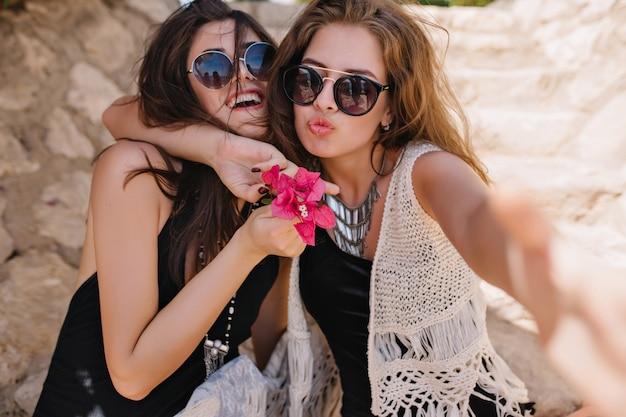 Śliczna śliczna Dziewczyna W Modnym Naszyjniku I Dzianinowym Stroju, Obejmująca Roześmianego Przyjaciela, Trzymającego Różowe Kwiaty. Dwie Niesamowite Siostry W Stylowych Okularach Przeciwsłonecznych Wygłupiające Się Na Wakacjach Na Dworze Darmowe Zdjęcia