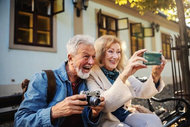 Śliczna Starsza Para Siedzi Na ławce I Robi Selfie. Mężczyzna Trzyma Aparat, Podczas Gdy Kobieta Trzyma Telefon Komórkowy. Premium Zdjęcia