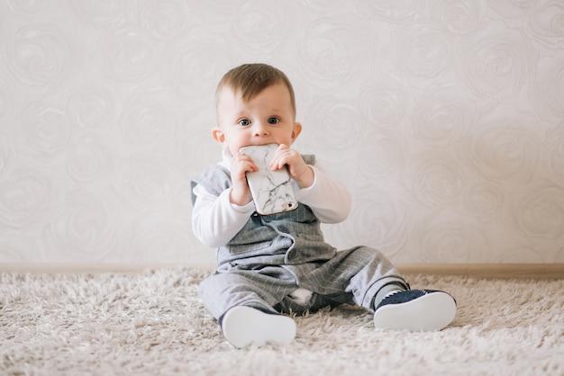 Śliczna Szczęśliwa Chłopiec W Eleganckim Dżentelmenu Kostiumu Obsiadaniu Na Bielu Premium Zdjęcia