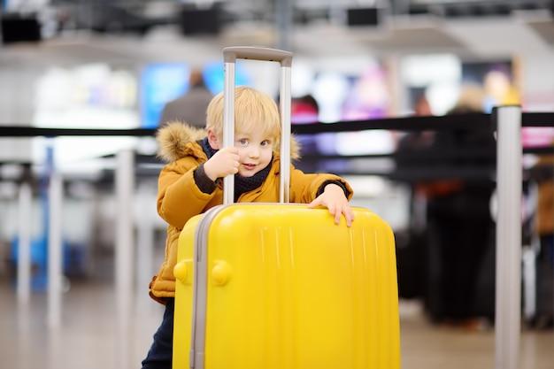 Śliczna Szczęśliwa Chłopiec Z Dużą żółtą Walizką Przy Lotniskiem Międzynarodowym Przed Lotem Premium Zdjęcia