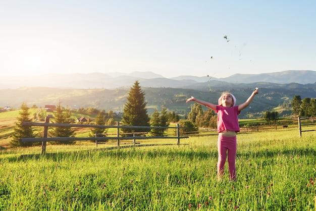 Śliczna szczęśliwa mała dziewczynka bawić się outdoors w gazonie i podziwia góra widok. skopiuj miejsce na tekst Premium Zdjęcia