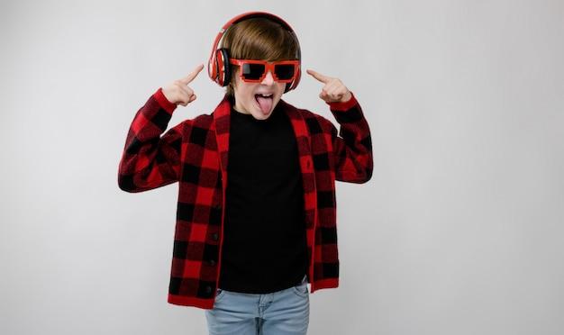 Śliczna ufna mała caucasian chłopiec w oszukiwać koszula w kratkę w okularach przeciwsłonecznych słucha muzyka w hełmofonach na szarym tle Premium Zdjęcia