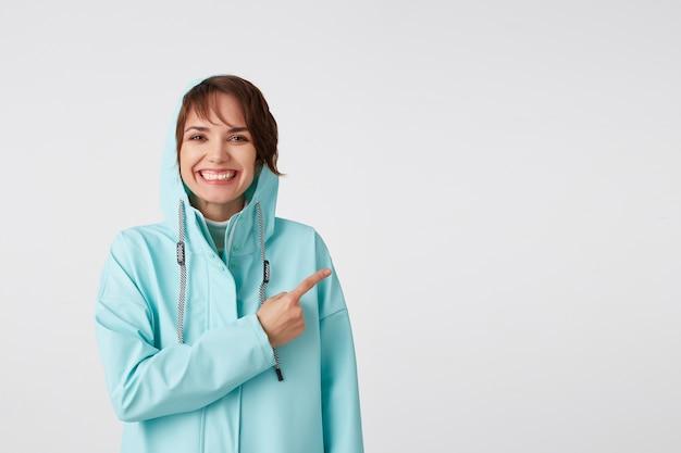 Śliczna Uśmiechnięta, Krótkowłosa, Kręcona Dama W Niebieskim Płaszczu Przeciwdeszczowym, Chce Zwrócić Uwagę Na Miejsce Po Prawej Stronie I Wskazując Na Niego, Stoi Na Białym Tle. Darmowe Zdjęcia
