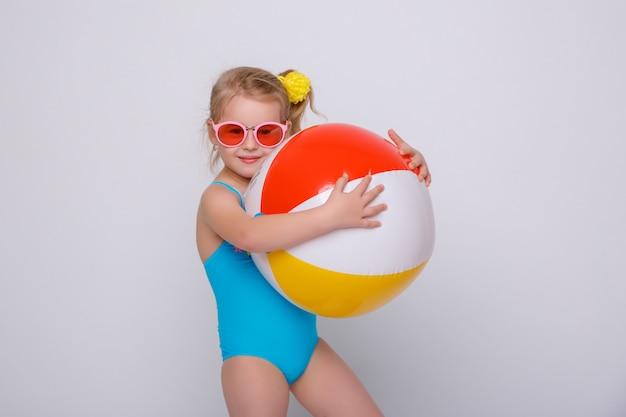 Śliczna Uśmiechnięta Mała Dziewczynka W Swimsuit Z Gumowym Pierścionkiem Odizolowywającym Na Bielu Premium Zdjęcia