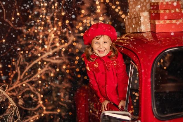 Śliczna Wesoła Dziewczyna W Pobliżu Czerwonego Samochodu Bożego Narodzenia łapiącego śnieg Rękami Premium Zdjęcia