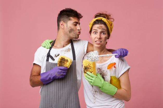 Śliczne Coupe: Przystojny Mężczyzna Obejmujący żonę, Który Chce Ją Pocałować, Pomagając Jej Posprzątać Dom Darmowe Zdjęcia