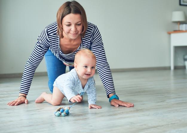 Śliczne Dziecko I Młoda Matka Pełzające W Domu Premium Zdjęcia