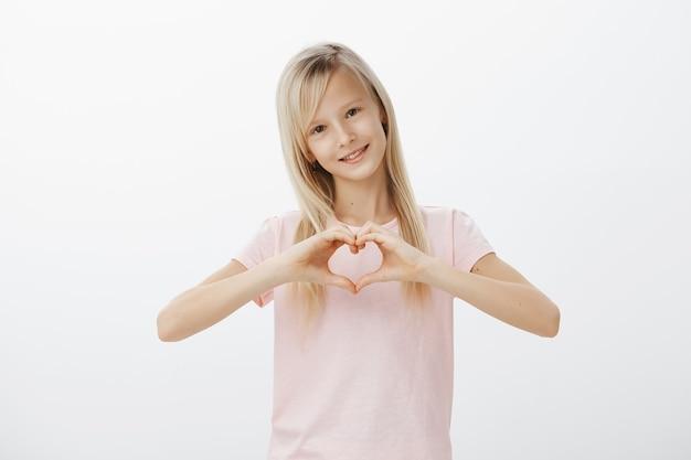 Śliczne Dziecko Pokazuje Gest Serca I Uśmiecha Się Darmowe Zdjęcia