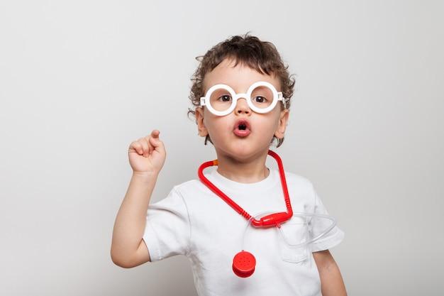 Śliczne I Zabawne Kręcone Dziecko W Okularach Ze Stetoskopem, Chłopiec W Garniturze Lekarza Pokazuje Palcem Widza. Pytający Wygląd. Czy Zostałeś Zaszczepiony Odosobniony. Premium Zdjęcia