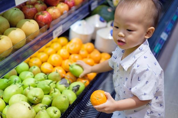 Śliczne Małe Azjatyckie 18 Miesięcy / 1-letni Maluch Chłopiec Dziecko Zakupy W Supermarkecie Premium Zdjęcia