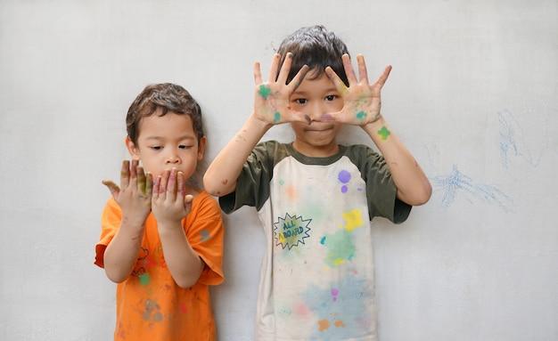 Śliczne małe azjatyckie bractwo dwóch chłopców gra zabawne kolory w czasie kreatywności Premium Zdjęcia