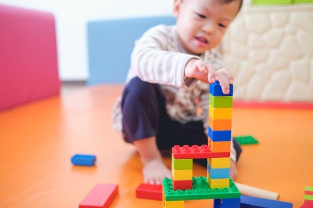 Śliczne Małe Azjatyckie Dziecko W Wieku 2-3 Lat, Maluch, Bawiące Się Bawiące Się Kolorowymi Klockami Z Tworzywa Sztucznego W Szkole, Przedszkolu, Salonie, Zabawkach Edukacyjnych Dla Małych Dzieci Premium Zdjęcia