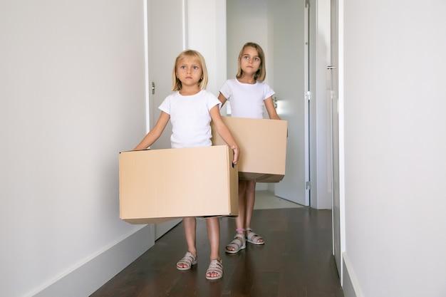Śliczne śliczne Dziewczyny Poruszające Się Po Nowym Mieszkaniu, Niosące Kartonowe Pudła Na Korytarzu Darmowe Zdjęcia