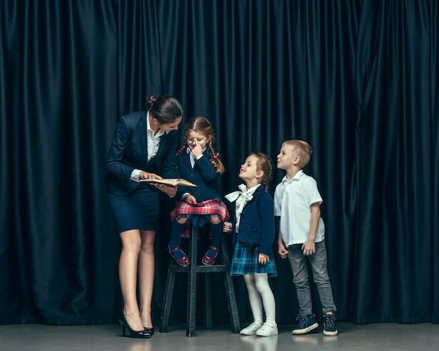 Śliczne Stylowe Dzieci W Ciemnym Studio. Piękne Nastolatki I Chłopak Stojący Razem Darmowe Zdjęcia
