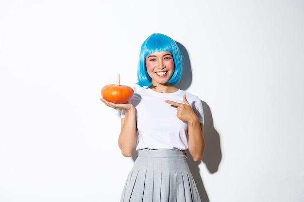 Śliczne Uśmiechnięte Azjatyckie Kobiety W Niebieskiej Peruce Palcem Wskazującym Na Małą Dyni, świętuje Halloween, Stojąc. Darmowe Zdjęcia