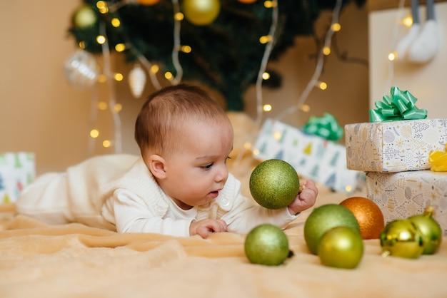Śliczne uśmiechnięte dziecko leży pod świąteczną choinką i bawi się prezentami Premium Zdjęcia