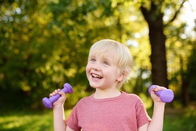 Ślicznej chłopiec podnośni dumbbells outdoors Premium Zdjęcia