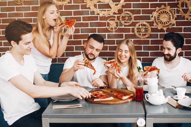 Śliczni przyjaciele w kawiarni je pizza Darmowe Zdjęcia