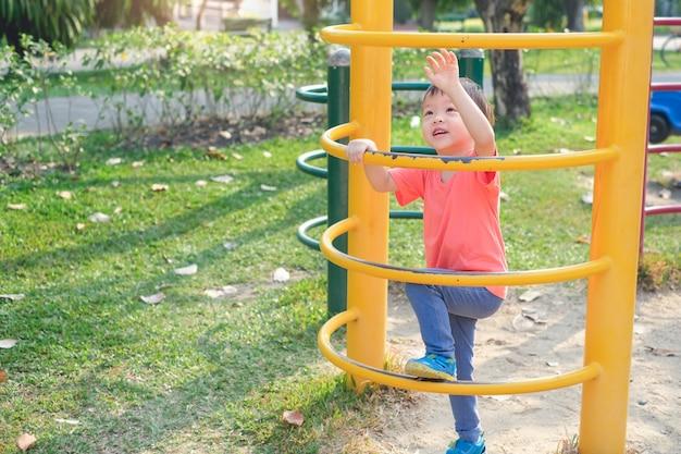 Śliczny Azjatycki 3 Lat Berbecia Chłopiec Dziecko Ma Zabawę Próbuje Wspinać Się Na Wspinaczkowej Ramie Przy Plenerowym Boiskiem Premium Zdjęcia
