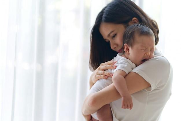 Śliczny azjatycki dziecięcy dziecko na matek rękach stoi w pokoju blisko okno. Premium Zdjęcia