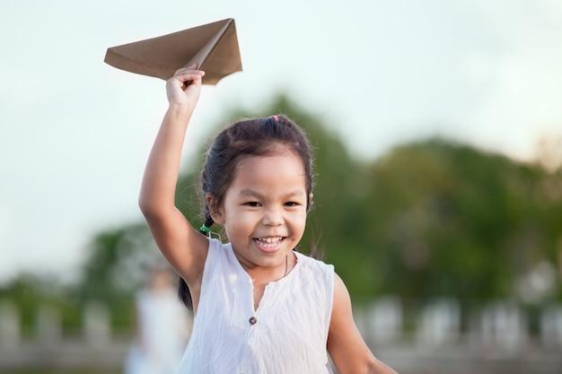Śliczny Azjatykci Dziecko Dziewczyny Bieg I Bawić Się Zabawkarski Papierowy Samolot W Polu W Rocznika Koloru Brzmieniu Premium Zdjęcia