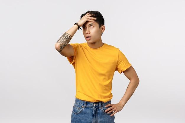 Śliczny Azjatykci Mężczyzna Uderza Pięścią W Czoło W żółtej Koszulce Premium Zdjęcia