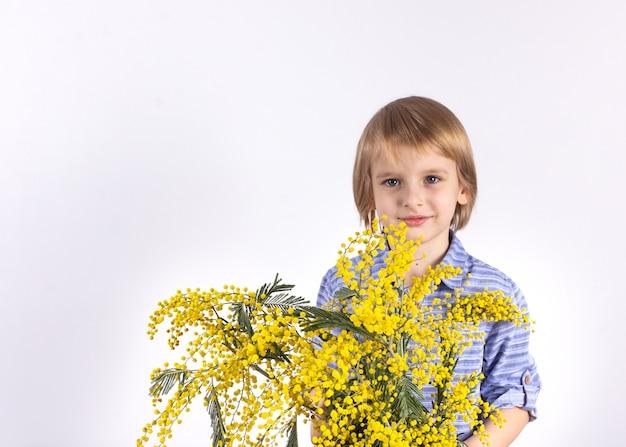 Śliczny chłopiec trzyma bukiet żółta mimoza. prezent dla mamy. gratulacje 8 marca, dzień matki. Premium Zdjęcia