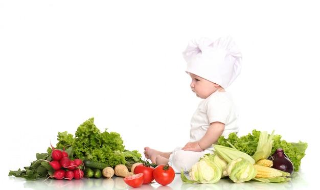 Śliczny Dziecko Szef Kuchni Z Różnymi Warzywami Darmowe Zdjęcia