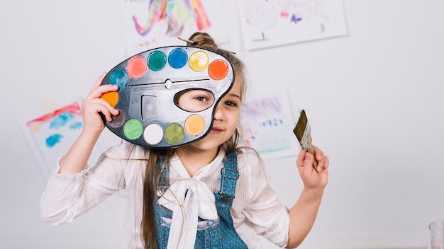 Śliczny dziewczyny obsiadanie z paletą i farby muśnięciem Darmowe Zdjęcia
