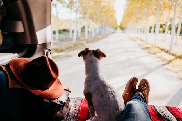 Śliczny Jack Russell Pies I Kobieta Iść Na Piechotę Relaksować W Samochodzie Dostawczym. Koncepcja Podróży Premium Zdjęcia