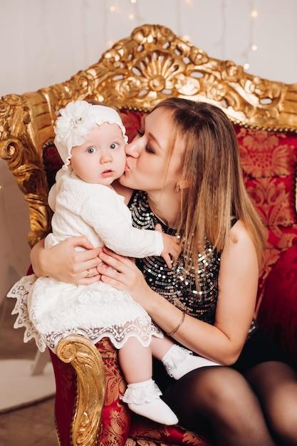 Śliczny małej dziewczynki obsiadanie z matką. czas świąt. Premium Zdjęcia
