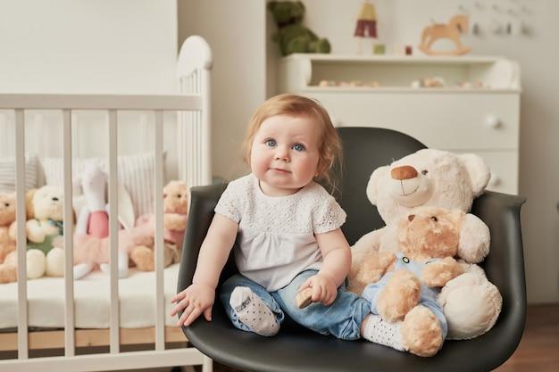 Śliczny Maluch Siedzi Na Krześle W Pobliżu Zabawek Premium Zdjęcia
