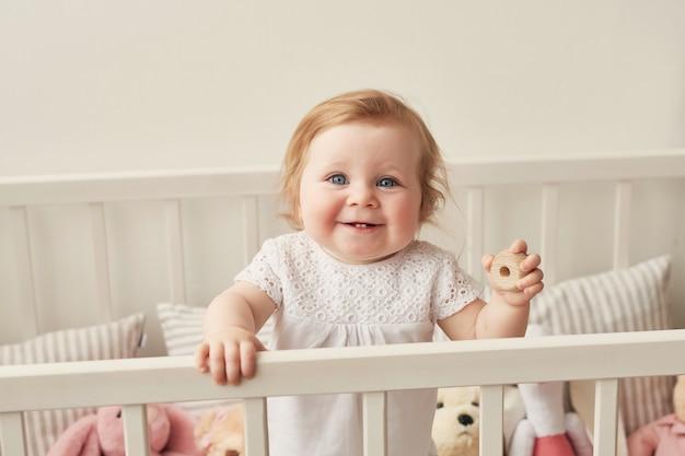 Śliczny Maluch Siedzi W Swoim łóżeczku W Pobliżu Zabawek Premium Zdjęcia