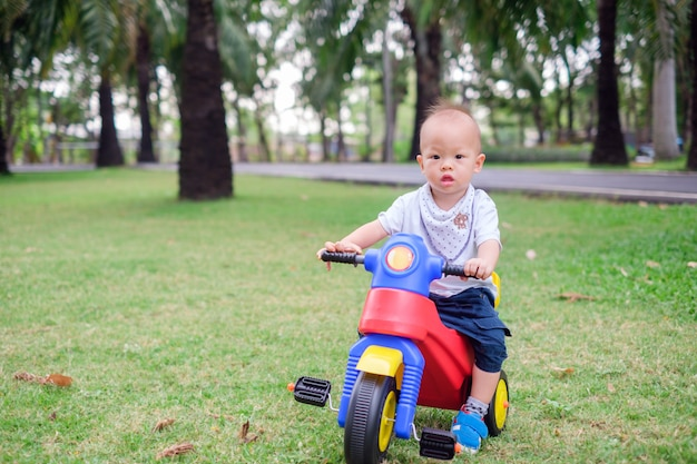 Śliczny mały azjatycki 1-letni berbeć chłopiec dziecko jedzie jego trójkołowiec w lato parku Premium Zdjęcia