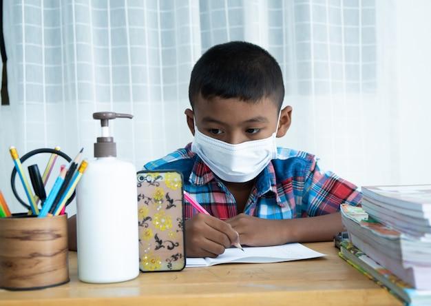Śliczny Mały Azjatykci Chłopiec Uczy Się Online Z Smartphone W Domu, Koronawirus Premium Zdjęcia