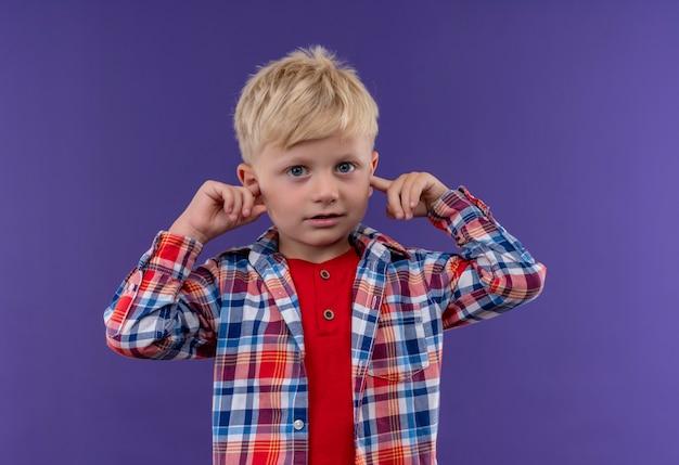 Śliczny Mały Chłopiec Z Blond Włosami W Kraciastej Koszuli, Trzymając Rękę Na Uszach Na Fioletowej ścianie Darmowe Zdjęcia