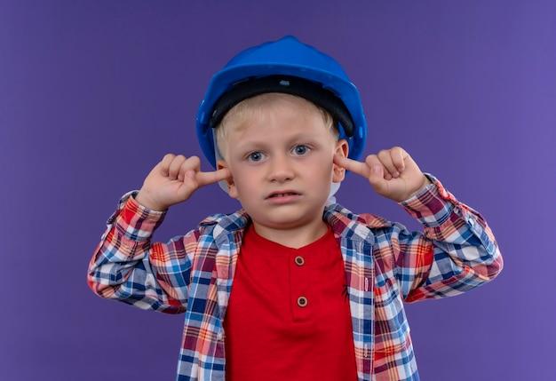Śliczny Mały Chłopiec Z Blond Włosami W Kraciastej Koszuli W Kasku, Trzymając Palce Na Uszach, Patrząc Na Fioletową ścianę Darmowe Zdjęcia
