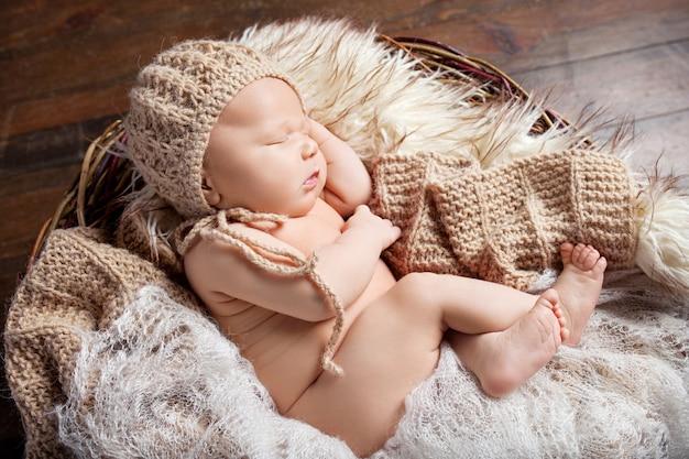 Śliczny Noworodek 20 Dni śpi W Koszyku Z Dzianinową Kratą. Portret Całkiem Nowonarodzonego Chłopca Premium Zdjęcia